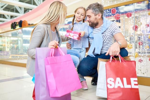Une famille achète des cadeaux pour une petite fille