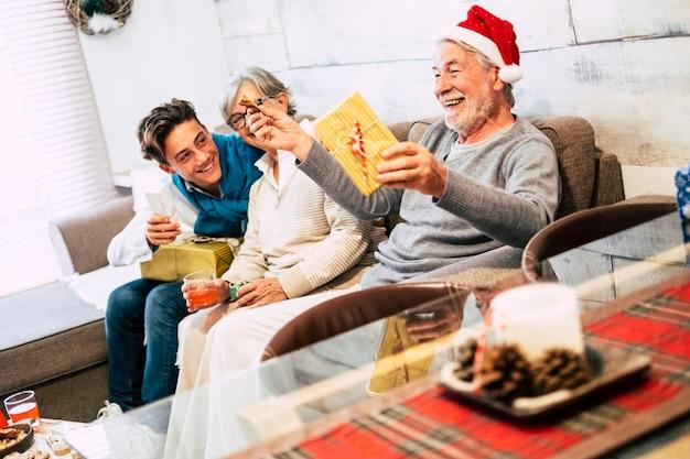 Famille avec adolescent et grands-pères assis sur le canapé à la maison le matin de noël en riant et en ouvrant leurs cadeaux avec beaucoup d'amour et d'affection
