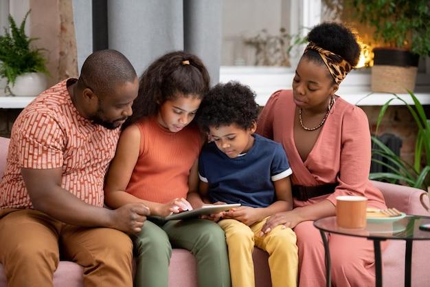 Famille africaine contemporaine composée d'un père, d'une mère et de deux enfants avec une tablette assise sur un canapé contre une fenêtre dans le salon et regardant un film