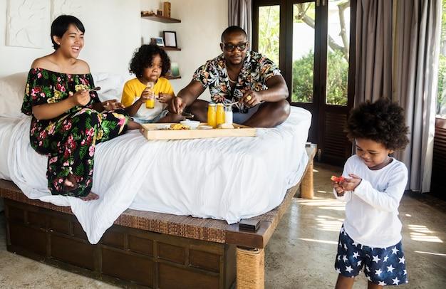 Famille africaine prenant son petit déjeuner au lit