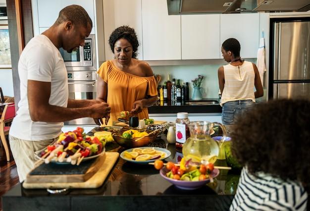 Famille africaine préparant un barbecue dans la cuisine ensemble