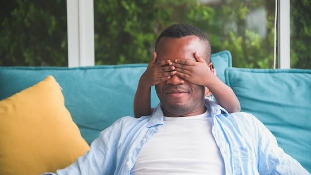 Famille africaine souriant père et fille main les yeux fermés pour jouer à la maison dans des vêtements décontractés