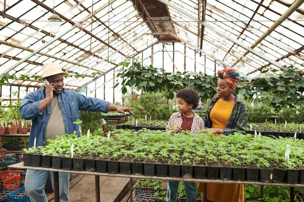 Famille africaine de trois légumes cultivant ensemble dans la serre chaude