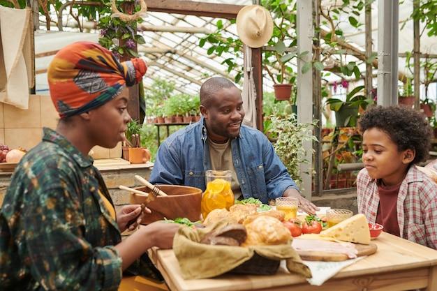 Famille africaine de trois personnes assises à table avec de la nourriture et déjeunant ensemble dans le jardin