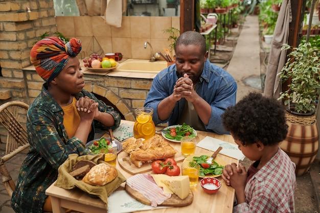 Famille africaine de trois personnes assises à table et priant ensemble avant le dîner