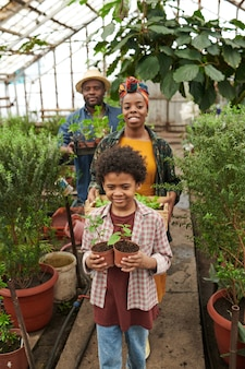 Famille africaine de trois personnes travaillant ensemble dans le jardin, ils plantent des plantes