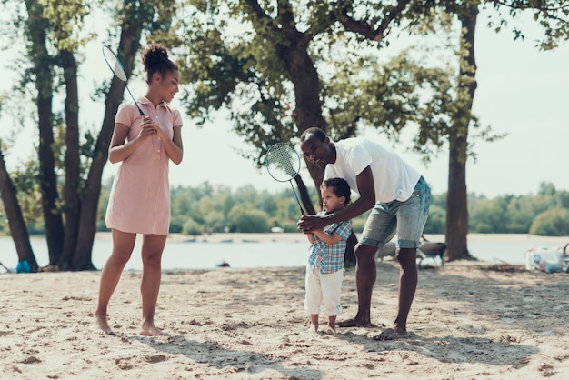 Une famille afro-américaine joue au tennis sur une rive sablonneuse