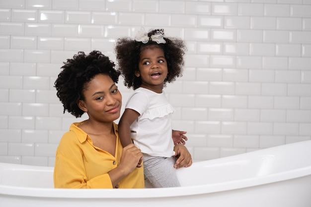 Famille afro-américaine, mère heureuse et petite fille s'amusant et jouant ensemble dans la salle de bain, fond de mur blanc