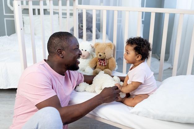 Famille afro-américaine, père et bébé parlant ou jouant dans la chambre à coucher à la maison, père heureux