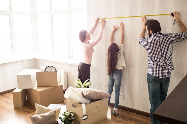 Une famille agréable et travailleuse travaille ensemble. l'homme et la femme mesurent la longueur du mur pendant que leur fille essaie de les aider.