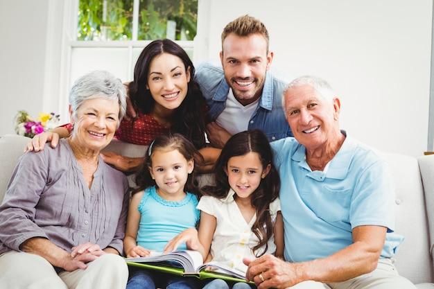 Famille aidant des filles en lisant un livre