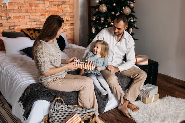 Famille aimante avec des cadeaux dans la chambre