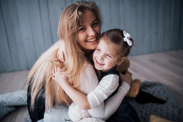 Famille aimante heureuse. mère et sa fille enfant fille jouant et étreignant