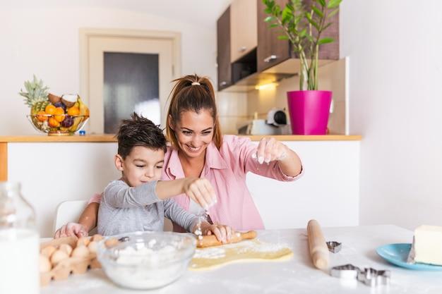 Une famille aimante et heureuse prépare une boulangerie ensemble. mère et enfant fils garçon préparent des biscuits et s'amusent dans la cuisine.