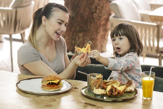 Famille aimante. maman avec jolie fille, manger de la restauration rapide dans un concept de café, de famille et de nutrition