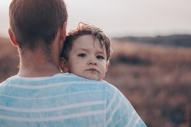 Famille aimante. père et son fils bébé garçon jouant et étreignant à l'extérieur. heureux papa et fils à l'extérieur. concept de la fête des pères.