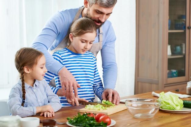 Famille aimante préparer une salade de légumes