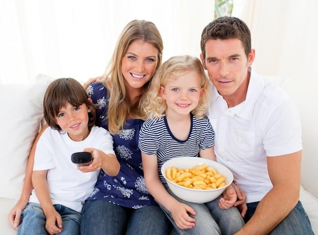 Famille aimante, regarder la télévision assis sur le canapé