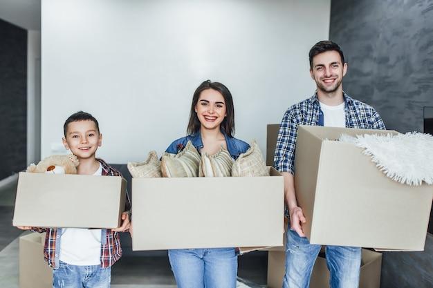 Famille aller dans une nouvelle maison tenant des boîtes avec des choses