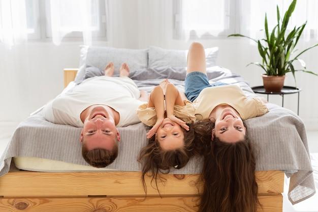 Famille allongée sur le lit avec leurs mains vers le bas