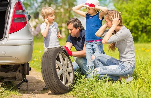 La famille amicale change le pneu de la voiture