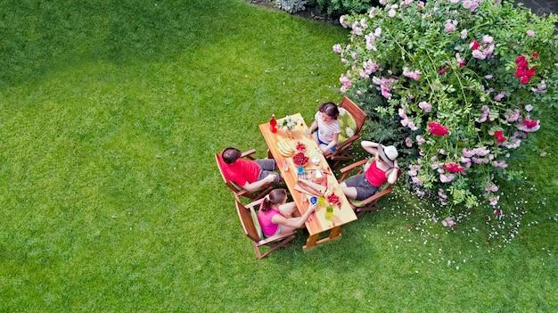 Famille et amis mangeant ensemble à l'extérieur lors d'une fête dans le jardin d'été vue aérienne de la table avec de la nourriture