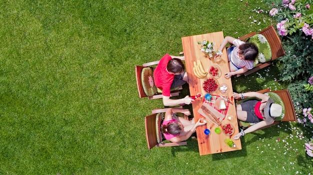 Famille et amis mangeant ensemble à l'extérieur lors d'une garden-party d'été