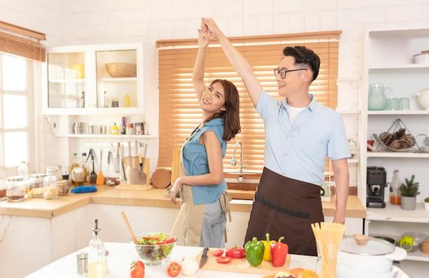 La famille asiatique aime cuisiner une salade et danser ensemble dans la cuisine à la maison.