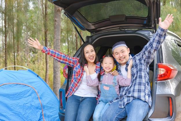 Une famille asiatique assise dans un coffre de voiture va camper en vacances. voyage en famille en voiture.