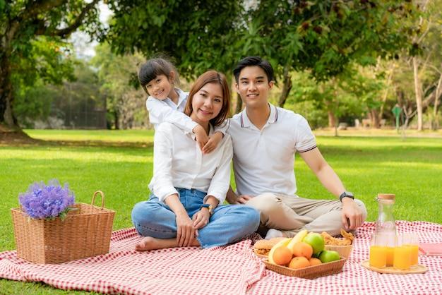 Famille asiatique ayant un pique-nique dans le parc