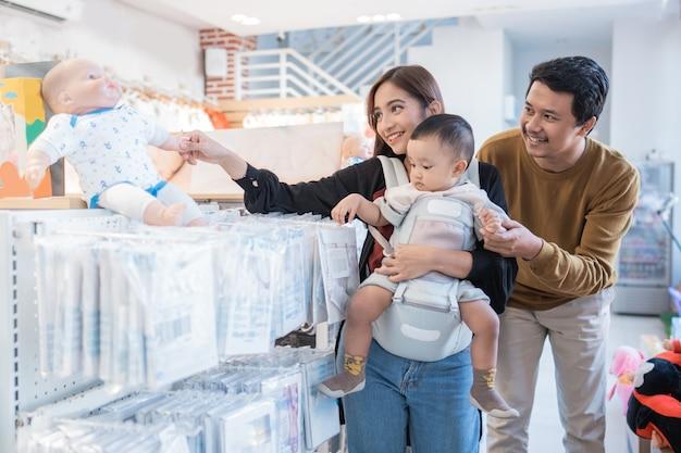Famille asiatique avec enfant achetant un produit pour bébé au centre commercial