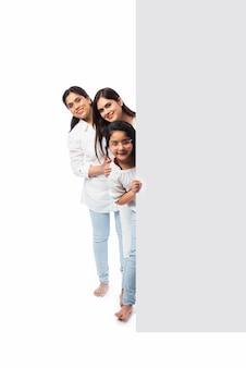 Famille asiatique indienne multigénérationnelle avec tableau blanc, pointant ou présentant une pancarte blanche vide