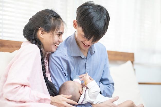 Famille asiatique jeune père et mère nourrir bébé garçon lait à la maison. portrait, de, asiatique, jeune couple, père, mère, tenue, nouveau né, nourrisson, alimentation, pépinière, jour mère, concept