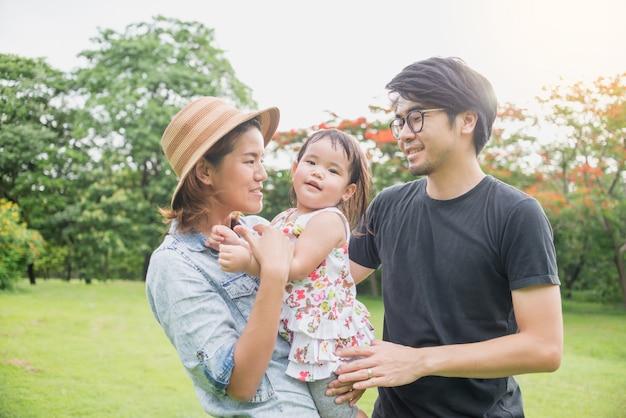 Famille asiatique avec jeunes enfants se détendre dans le parc en plein air en été.