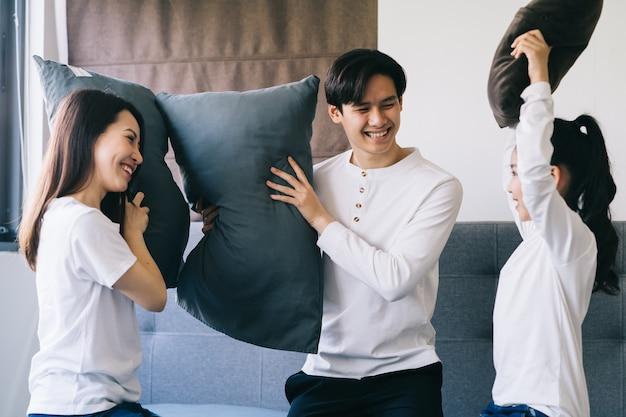 Famille asiatique joue au lit ensemble