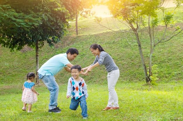 Famille asiatique jouissant de temps en plein air de qualité, les asiatiques jouant au beau coucher de soleil.