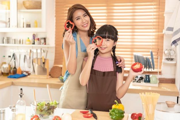 La famille asiatique, la mère et la fille aiment cuisiner préparer des salades ensemble dans la cuisine à la maison.