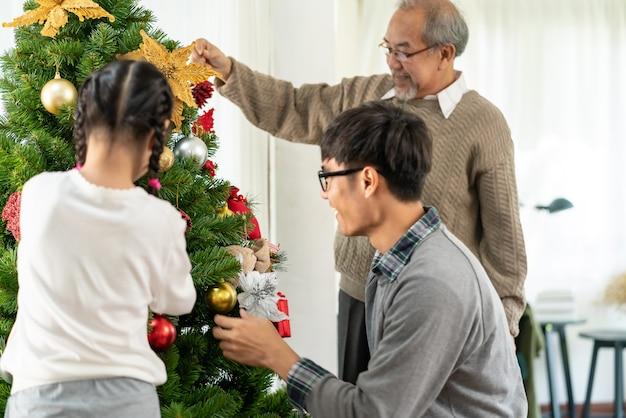 Famille asiatique multigénérationnelle décorant un arbre de noël.