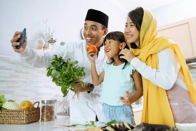 Une famille asiatique musulmane prend un selfie pendant la préparation du dîner iftar ensemble à la maison