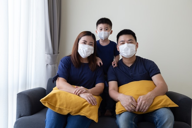 Famille asiatique portant un masque et assis ensemble dans le salon