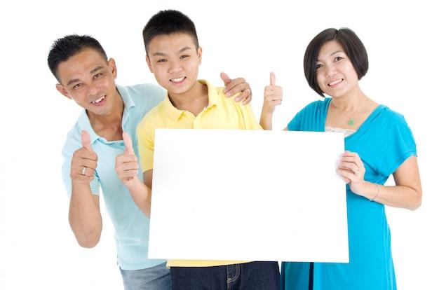 Famille asiatique tenant un tableau blanc blanc sur fond blanc.