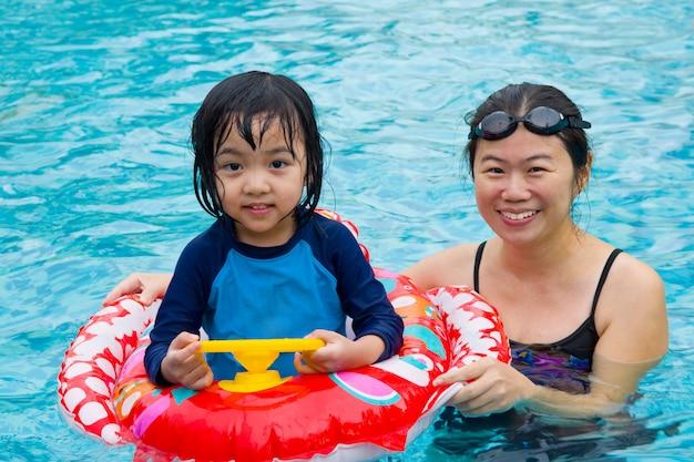 Famille asiatique en tube de bain jouant à la piscine