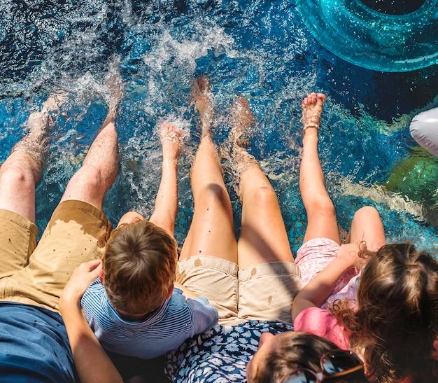 Famille assis au bord de la piscine