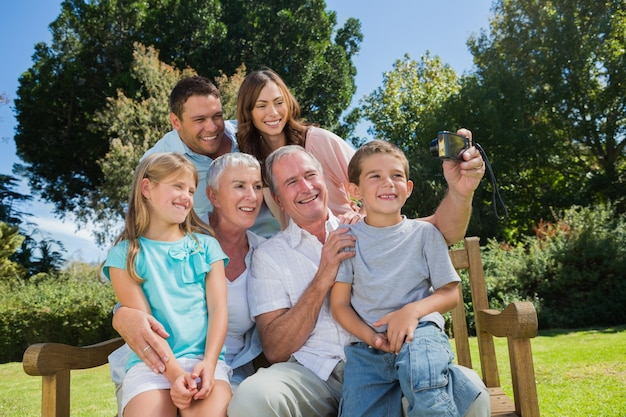 Famille assis sur un banc en prenant la photo d'eux-mêmes