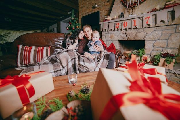 Famille assis sur le canapé vêtue d'une couverture et vu des cadeaux de table marron