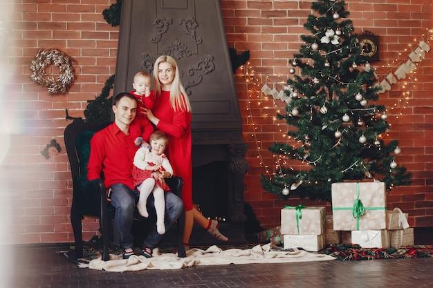 Famille assis à la maison près de sapin de noël