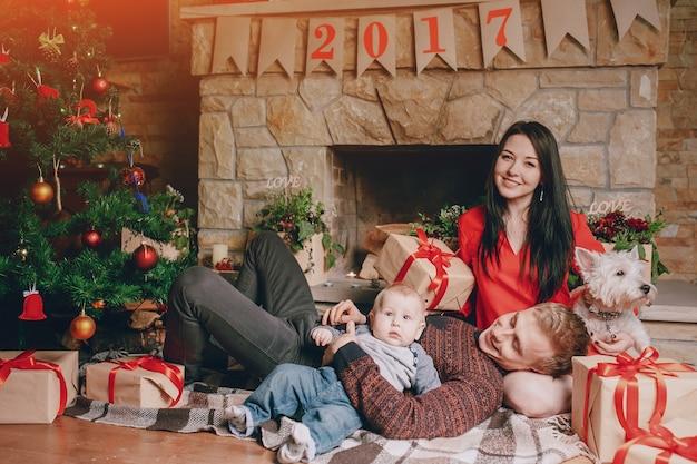 Famille assis sur le sol avec des cadeaux bruns et un arbre de noël