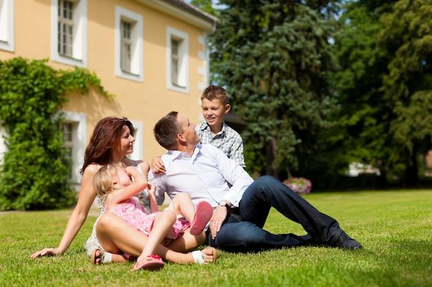 Famille assise dans l'herbe devant leur maison
