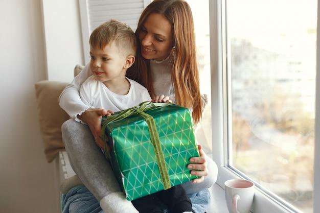 Famille assise à la maison avec des cadeaux
