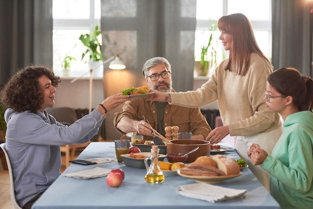 Famille assise à table, ils vont dîner dans la salle à manger à la maison
